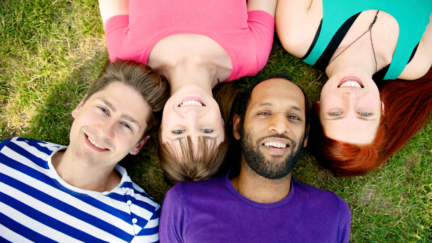 International students lie laughing on the meadow